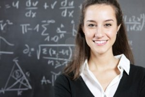 12577623-portrait-of-a-smiling-young-woman-college-student-or-teacher-in-front-of-a-blackboard